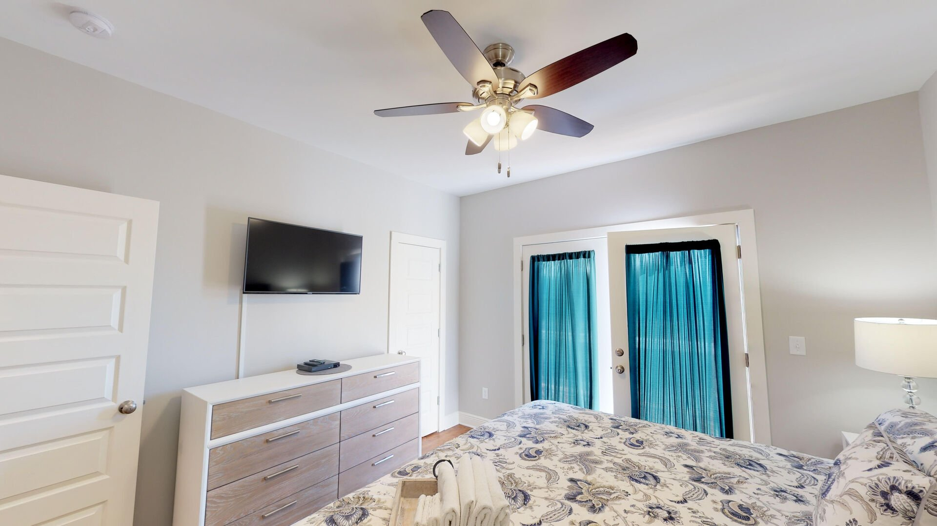 Large Bed, Door to the Balcony, TV,  Drawer Dresser, and Ceiling Fan.