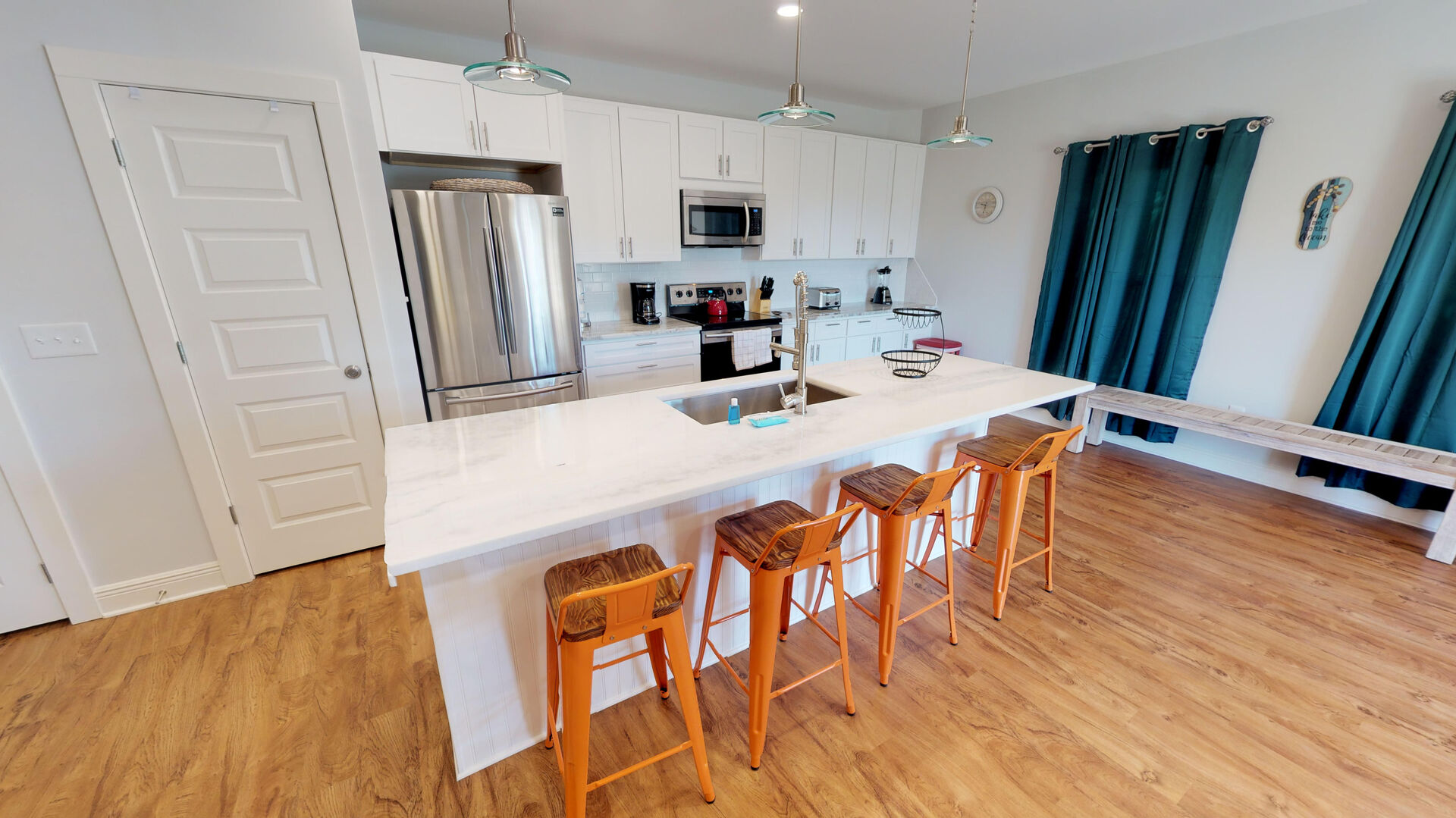 Kitchen Island with Stools, Refrigerator, Microwave, Toaster, and a Bench.