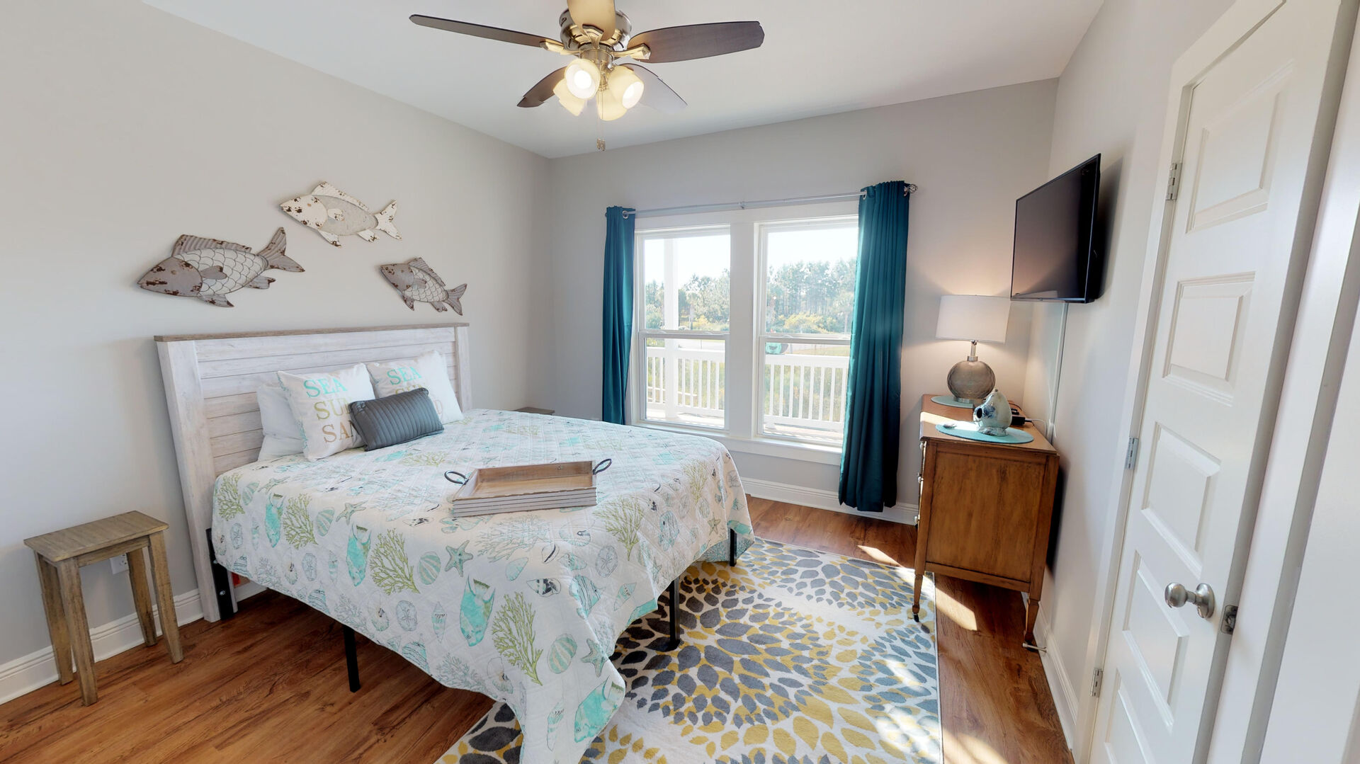 Large Bed, Buffet Console, TV, Windows, and Ceiling Fan.