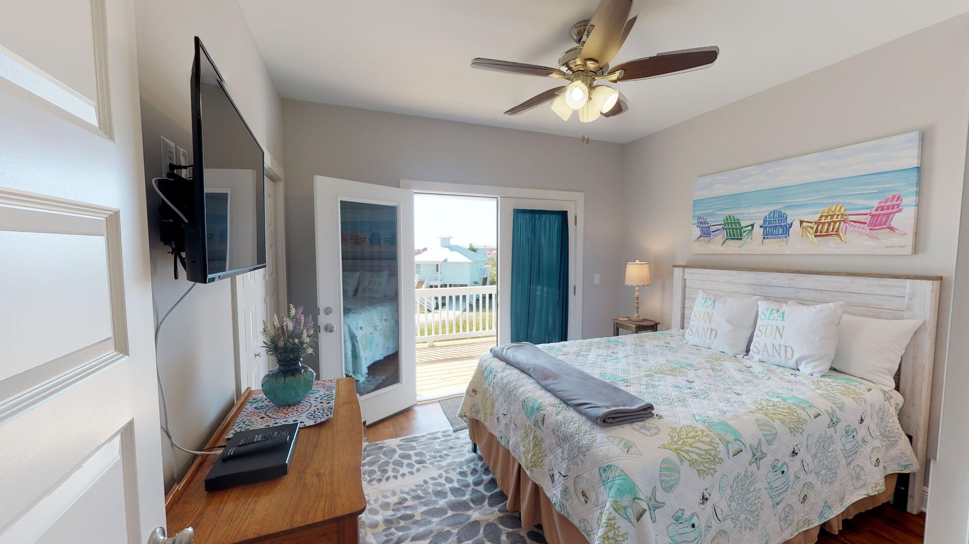 Bedroom with Large Bed, Buffet Console, TV, Ceiling Fan, and Door to the Balcony.