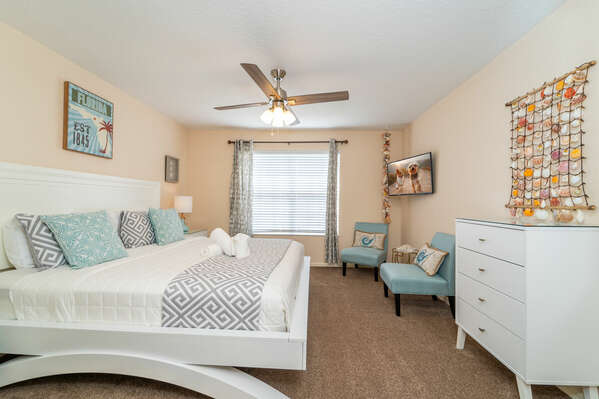 Second master bedroom is upstairs and features a king bed, two chairs to relax in, wall mounted flatscreen and a calm pastel blue tone