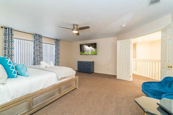 Alternative view of master bedroom showing double doors to landing, chairs to relax in and flatscreen TV