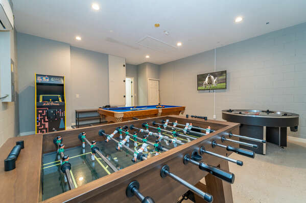Another photo of games room showing foosball table and retro arcade machine