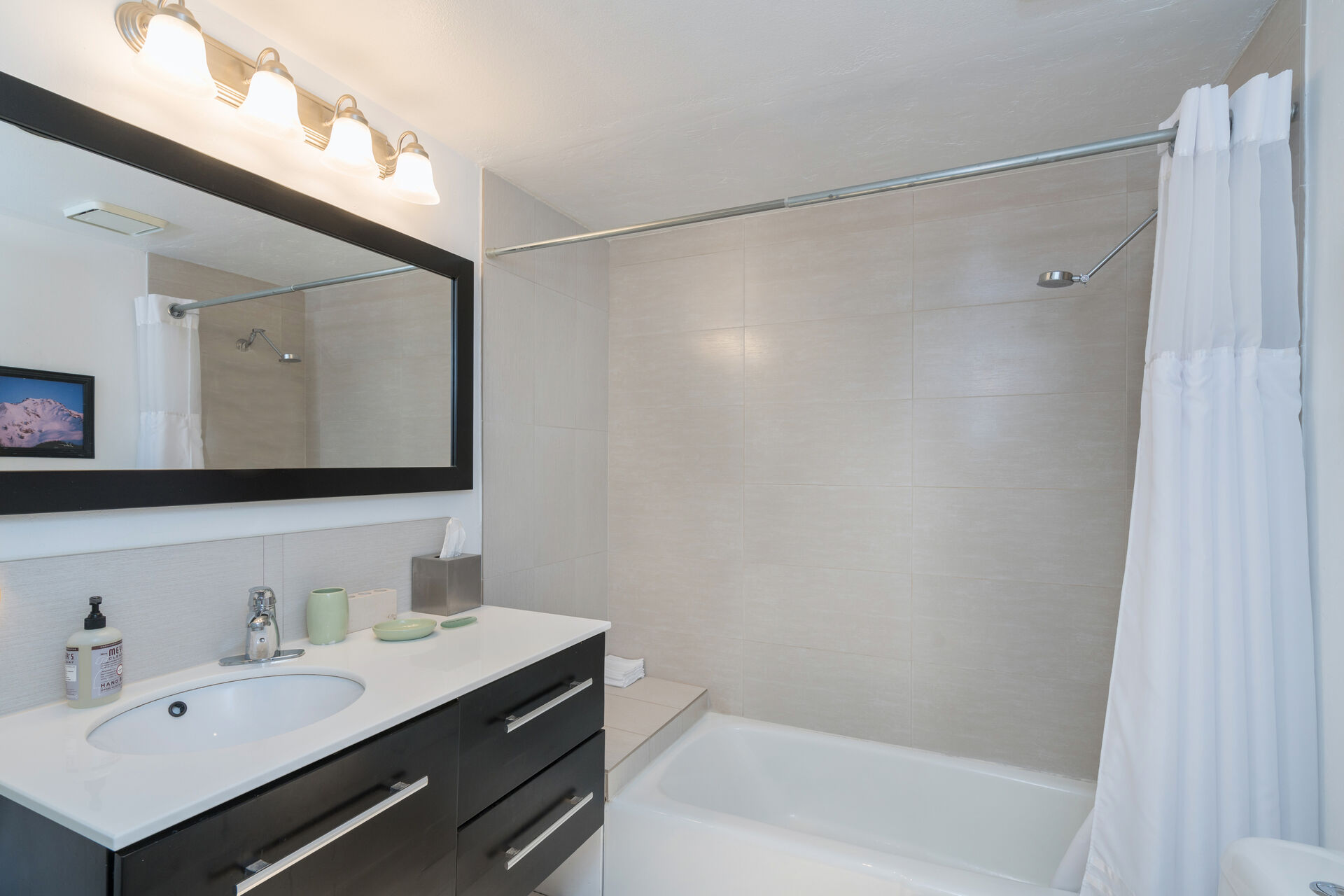 Vanity sink by a large shower in a bathroom.