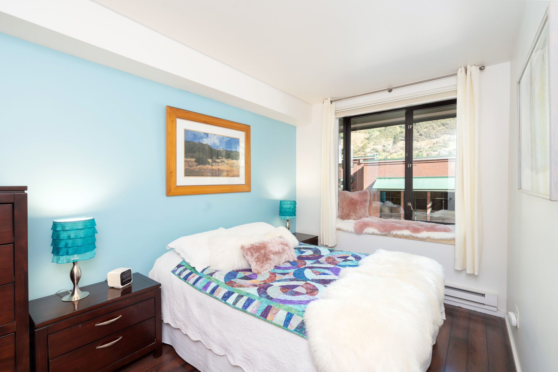 Bedroom with twin nightstands flanking a large bed made with colorful sheets.