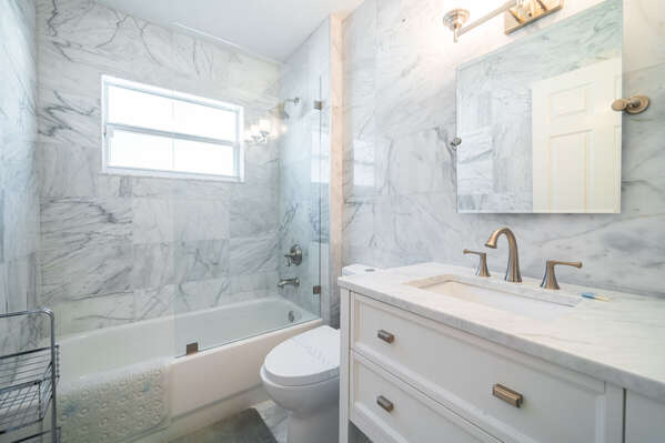 Shared family bathroom with single sink vanity and shower tub combo