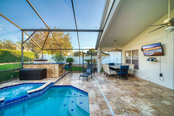 Pool view showing outdoor kitchen, seating and Roku TV