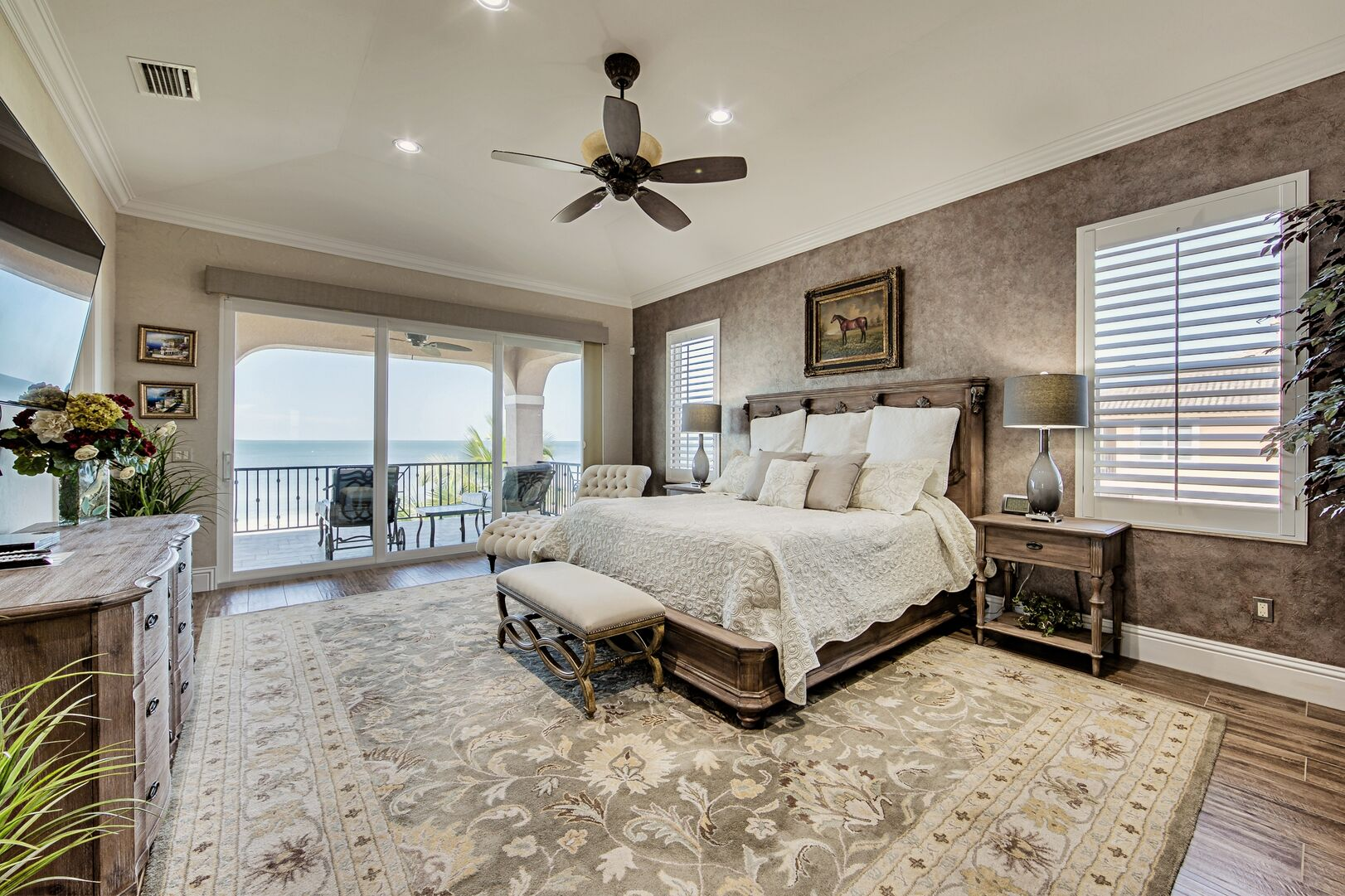 Large Bed, Nightstands, Bench, Ceiling Fan, and the Sliding Doors to the Balcony.