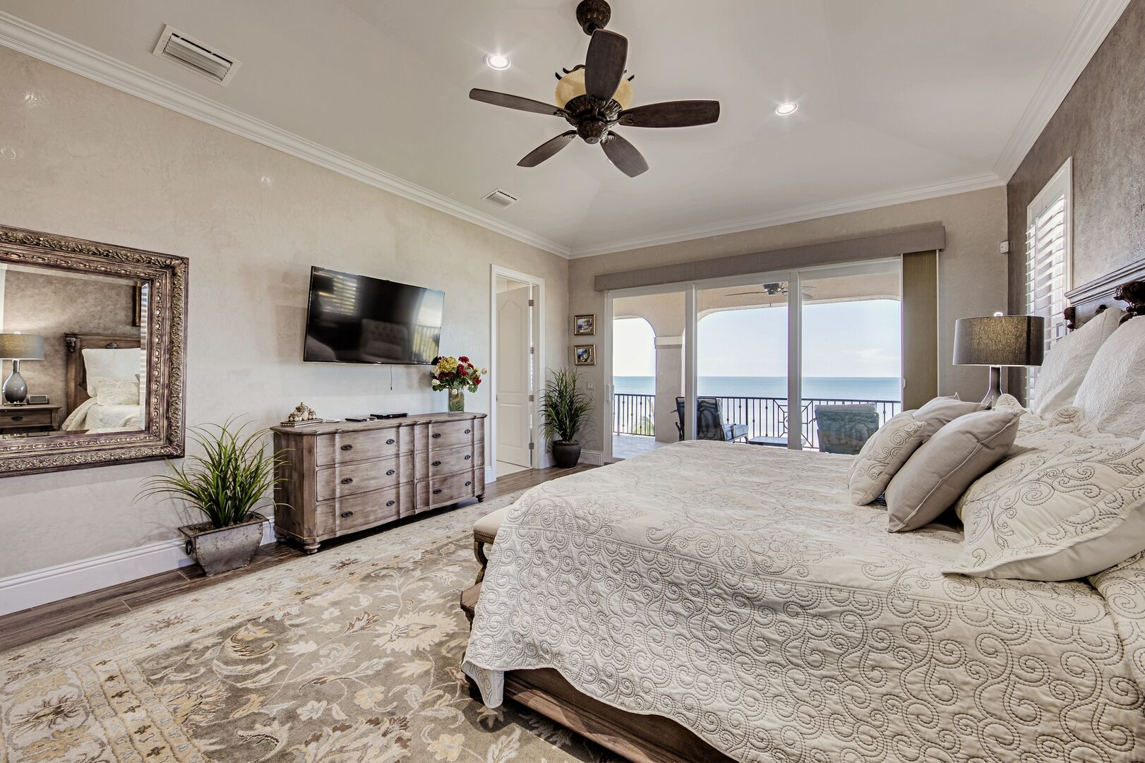 Large Bed, Dresser, TV, Nightstands, Ceiling Fan, and the Sliding Doors to the Balcony.
