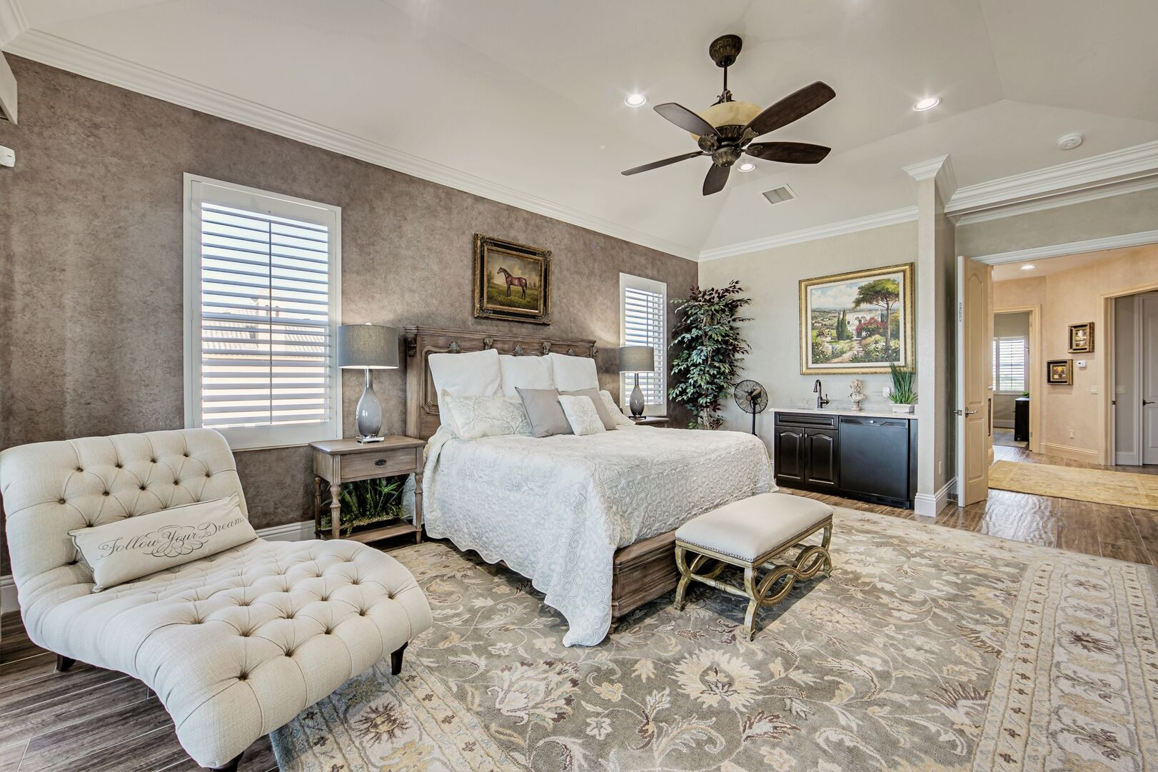 Large Bed, Chaise Lounge Sofa, Nightstands, Wet Bar, and Ceiling Fan.