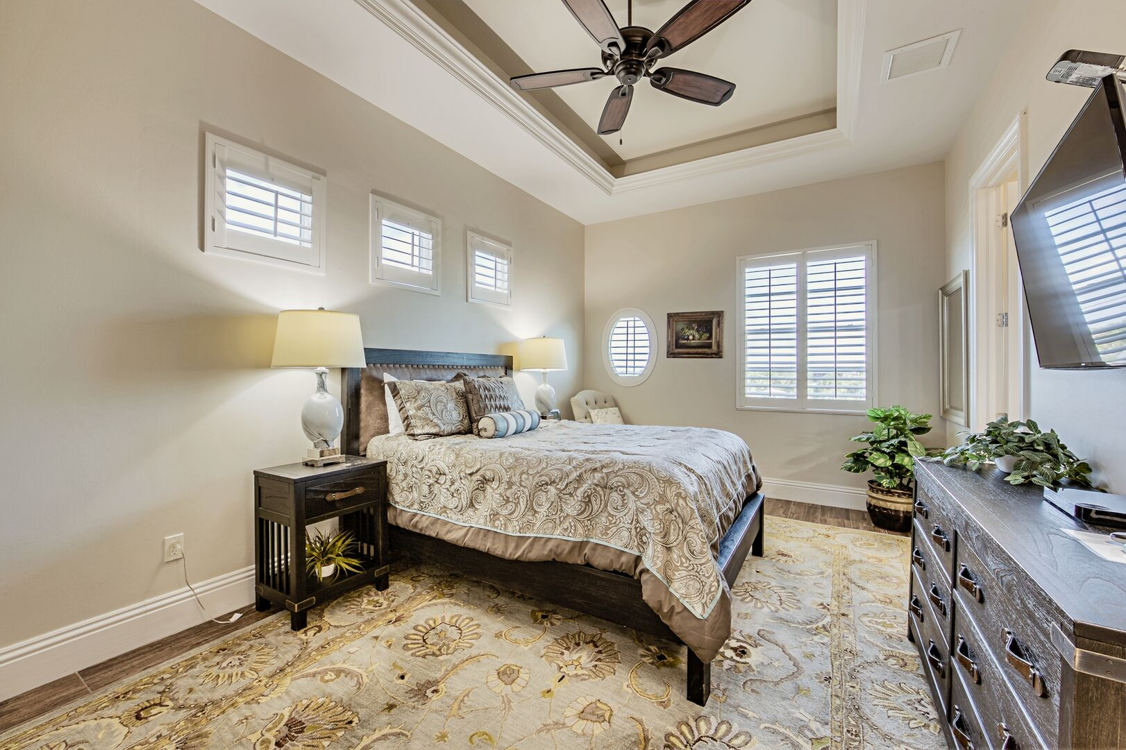 Drawer Dresser, TV, Large Bed, Ceiling Fan, Nightstands, and Table Lamps.