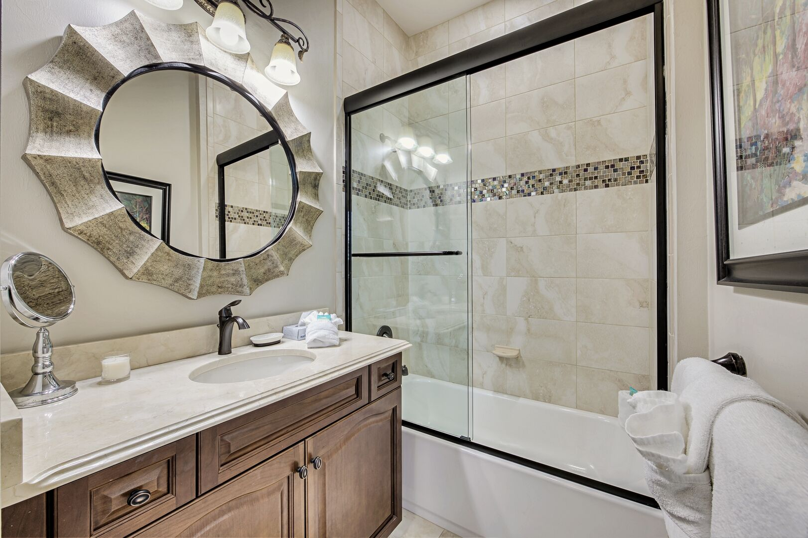 Shower-Tub Combo, Single Vanity Sink, Mirror, Towels, and Wall Lamp.