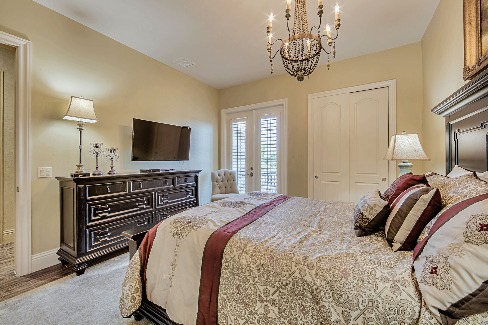 Large Bed, Drawer Dresser, TV, Closet, and the Window Doors to the Balcony.