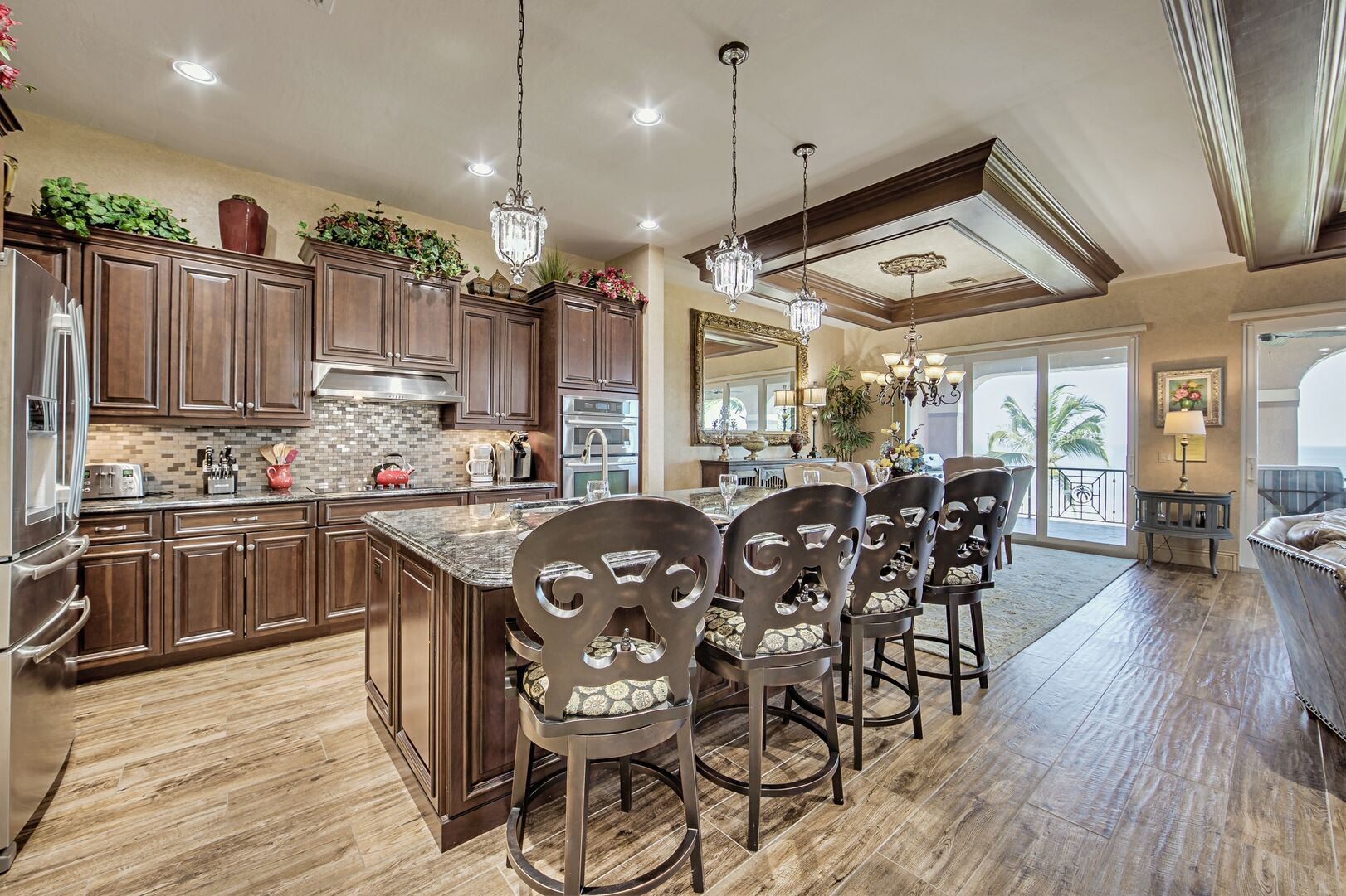 Kitchen with Island, High Chairs, Refrigerator, Dining Set and the Sliding Doors to the Balcony.
