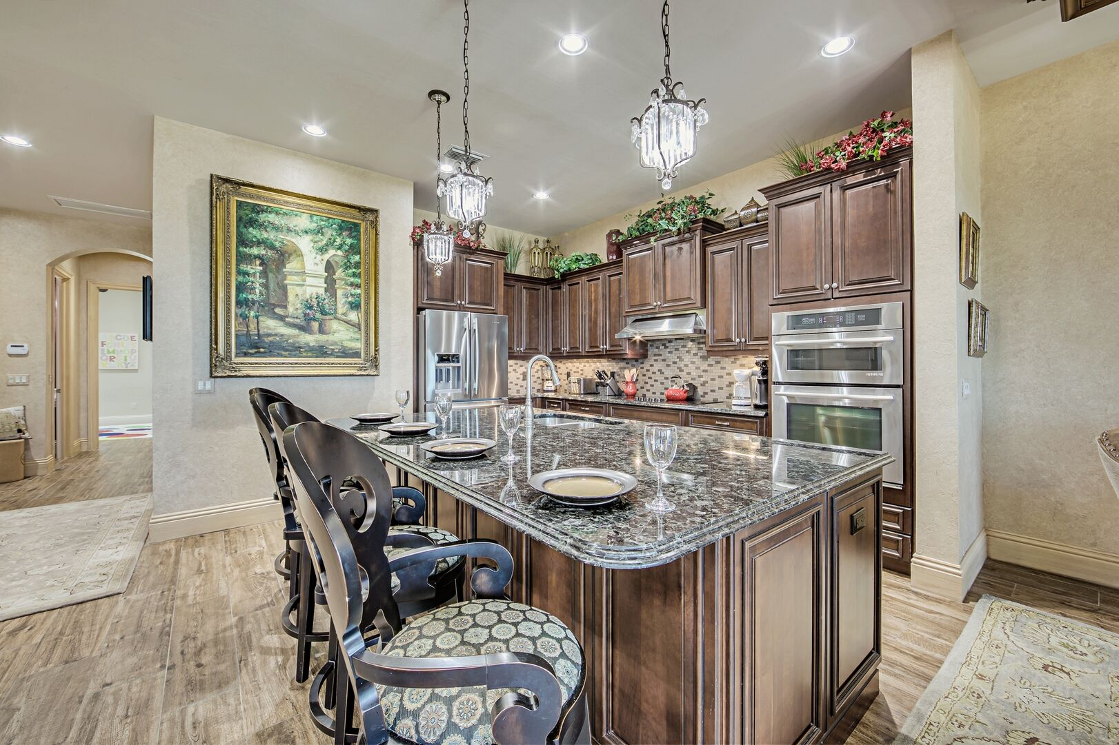 Kitchen with Island, High Chairs, Refrigerator, and Oven.