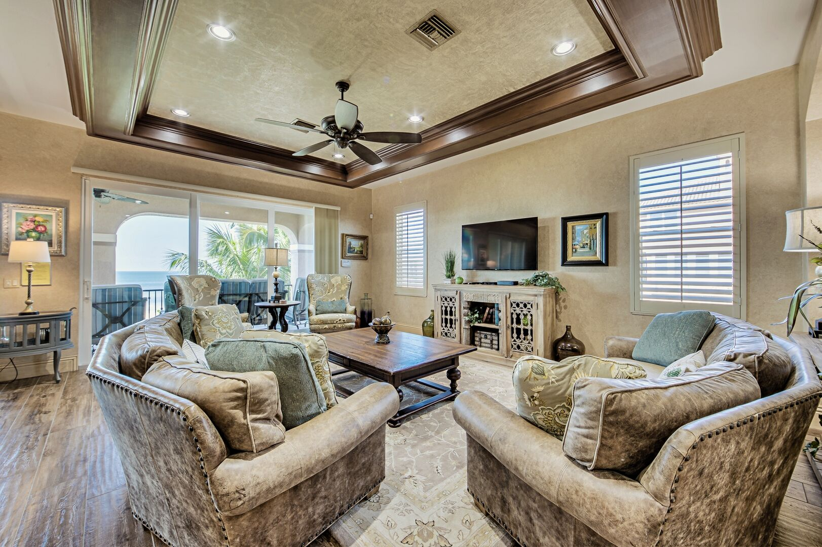 Sofas, Tables, TV, Ceiling Fan, and Sliding Doors to the Balcony with Gulf View.