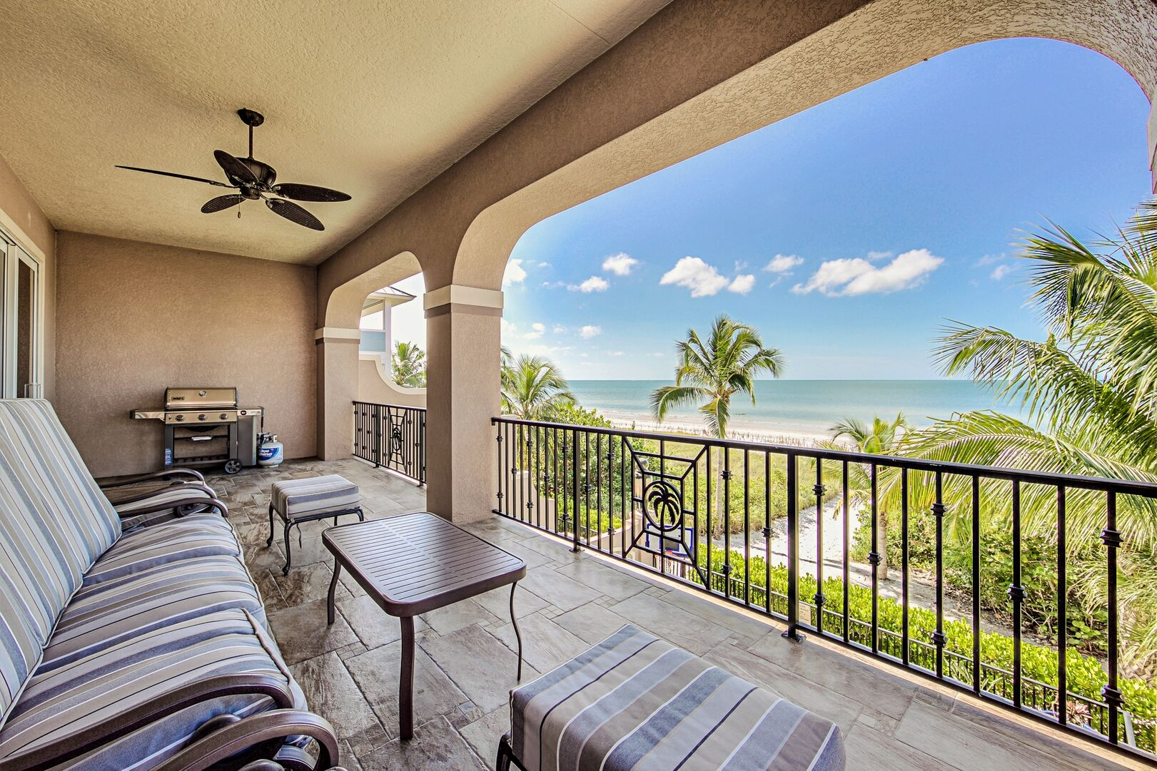 Spacious Balcony with BBQ Grill, Ceiling Fan, and Outdoor Seating Set.