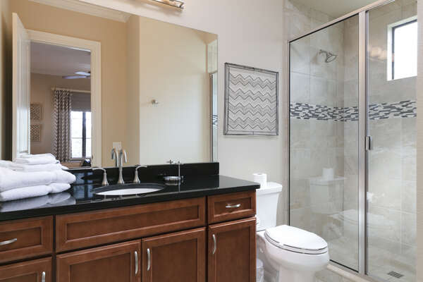 The ensuite bathroom has plenty of storage space and a walk-in shower