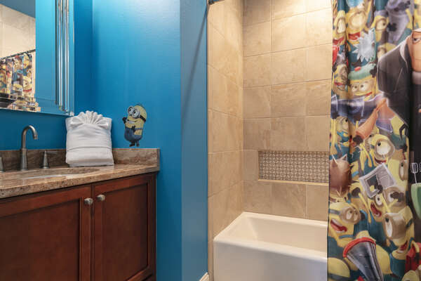 The ensuite bathroom matches the theme of the bedroom and has a shower/tub combo