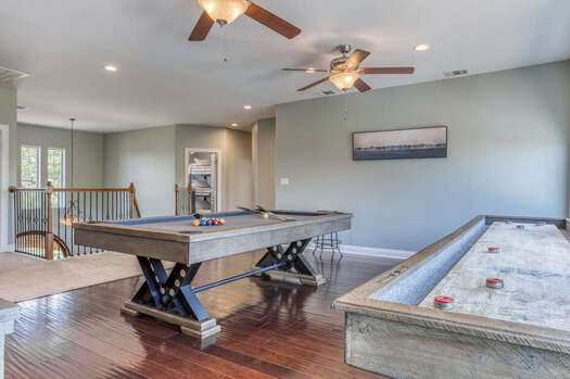 Upper Level Game Room with a Custom Pool Table and 14 Ft. Shuffleboard Table, a 65