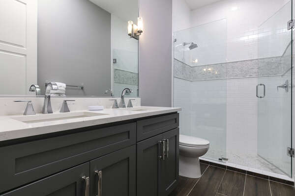 The ensuite bathroom with a dual vanity and walk-in shower