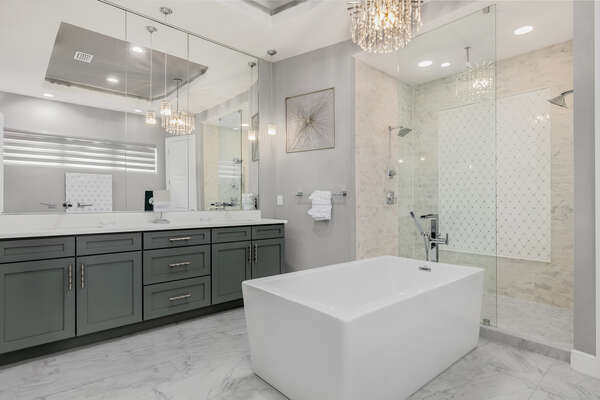 The large ensuite bathroom has a garden tub, dual vanity and a his and her shower