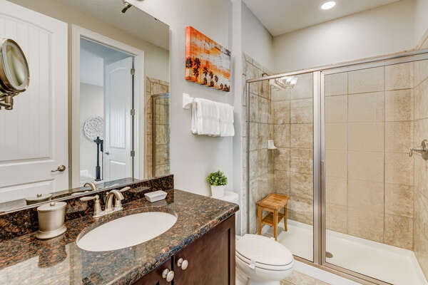The ensuite bathroom is complete with a shower stool and LED lighted makeup mirror