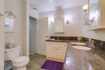 Guest bathroom with two sinks and a shower tub combo.