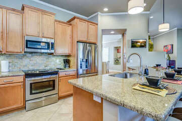 Fully Equipped Kitchen with Stainless Steel Appliances, Bar Seating for 6, and Granite Countertops