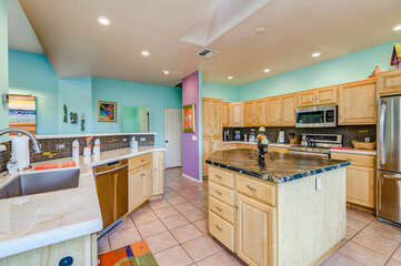 Spacious Kitchen with an Island, Stainless Steel Appliances and Marble Countertops