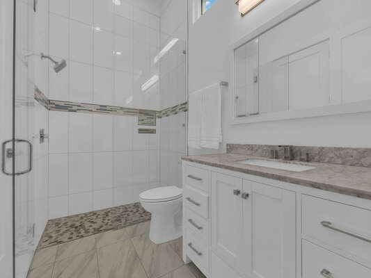 The bathroom has a tub/shower combination and beautiful marble countertops.