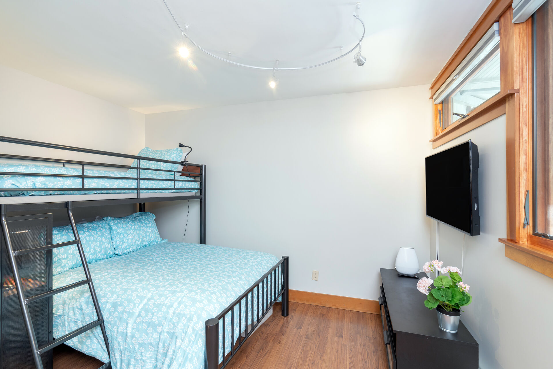 Guest bedroom with large bunk beds and mounted HD TV