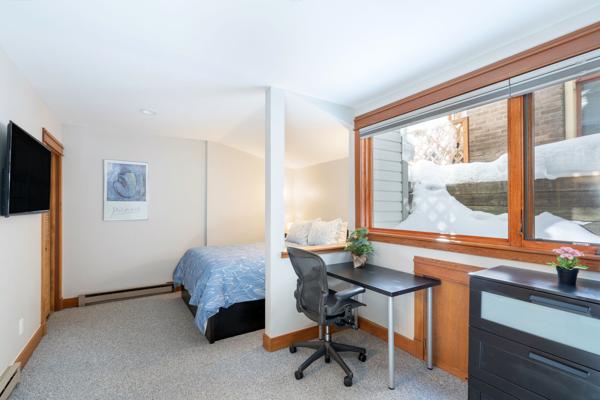 Room with bed and small desk to work from
