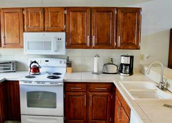 Full Kitchen with White Counter Tops and Appliances