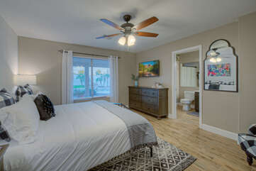 Spacious primary suite has a king bed, ceiling fan and TV