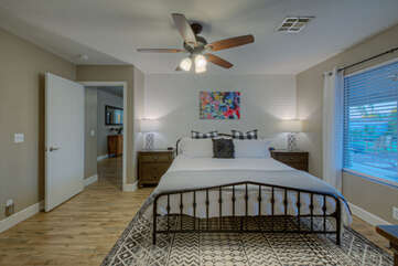 Primary suite includes a king bed, ceiling fan and TV