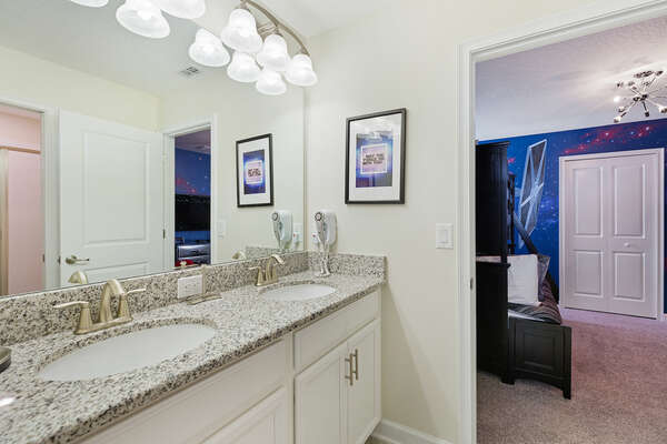 A Jack and Jill bathroom has a dual vanity and walk in shower