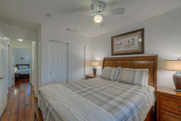 The second bedroom has a queen bed, ceiling fan and TV.