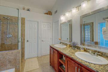 Modern primary bath has dual vanity sinks, a walk-in shower and garden tub.