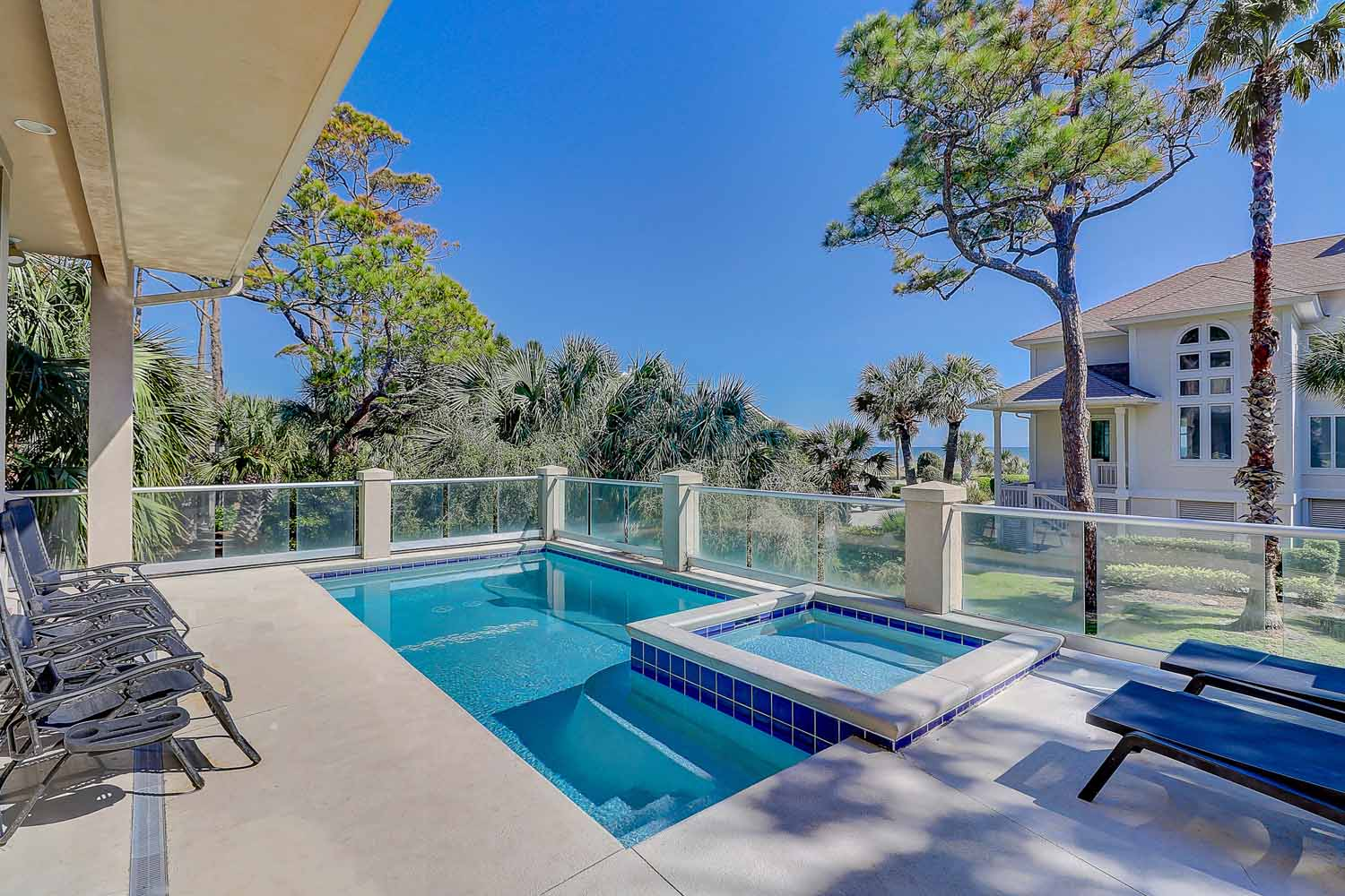 Elevated pool, kiddie pool and sun deck with view of ocean and 3 burner gas grill