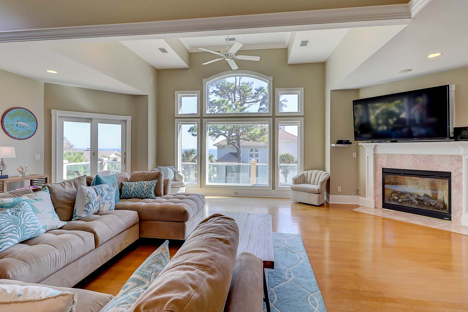 Large upper level living space is light and bright with updated furnishings, large TV, decorative fire place, large windows, tray ceilings and ceiling fans