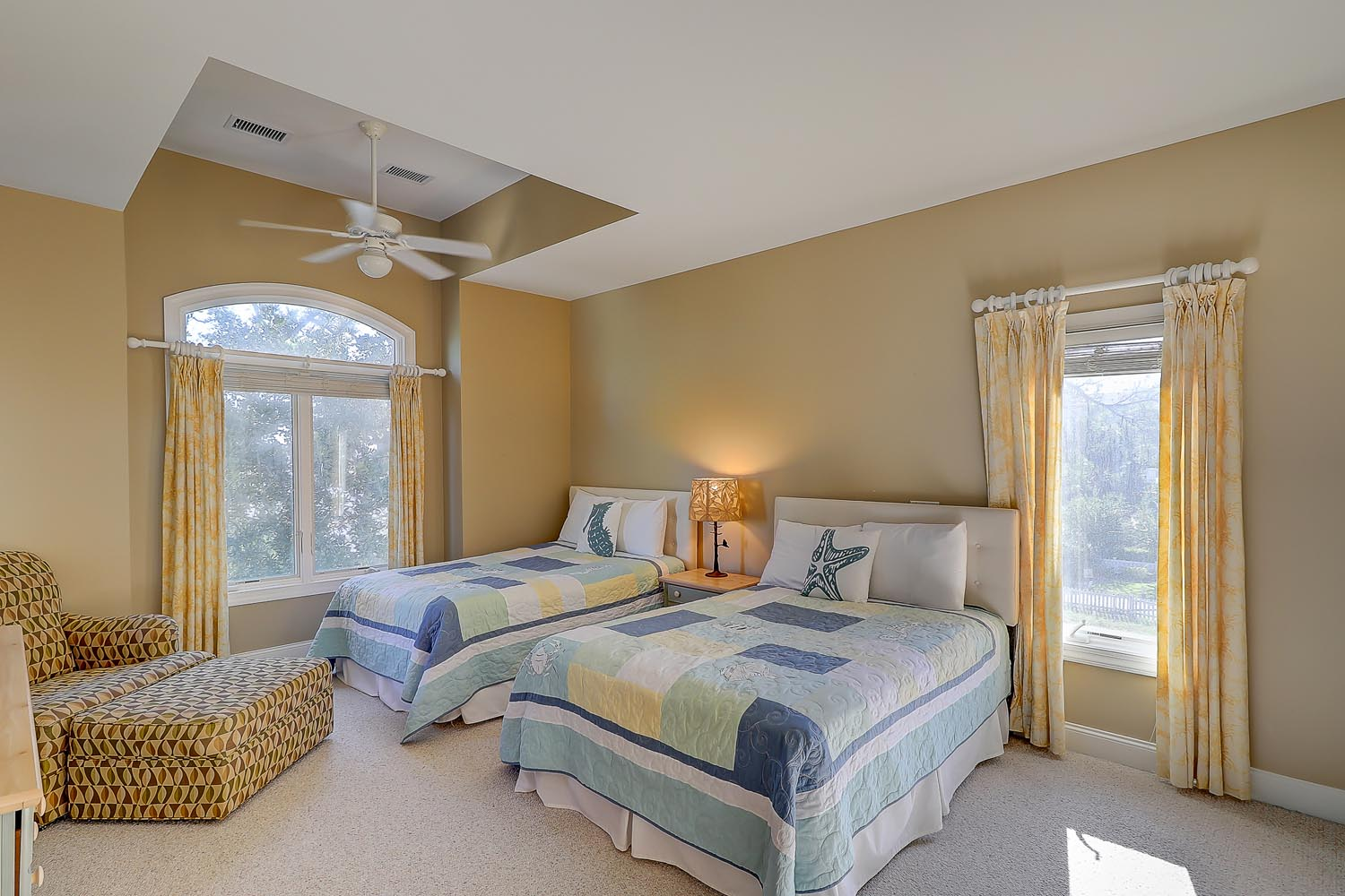 Upstairs ocean view  bedroom with 2 double beds, flat  panel TV and private en suite bath with tub shower combo