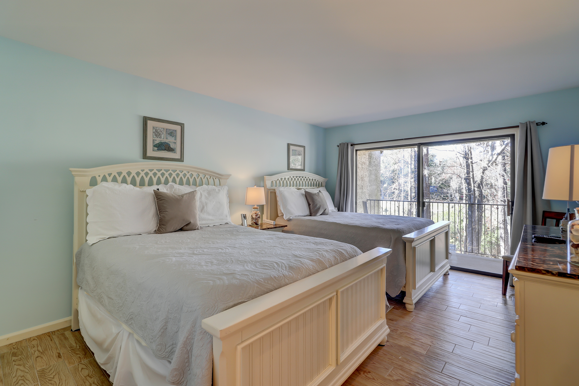 The guest bedroom features 2 queen beds, wall-mounted flat panel TV and access to a hall bathroom with tub/shower combo