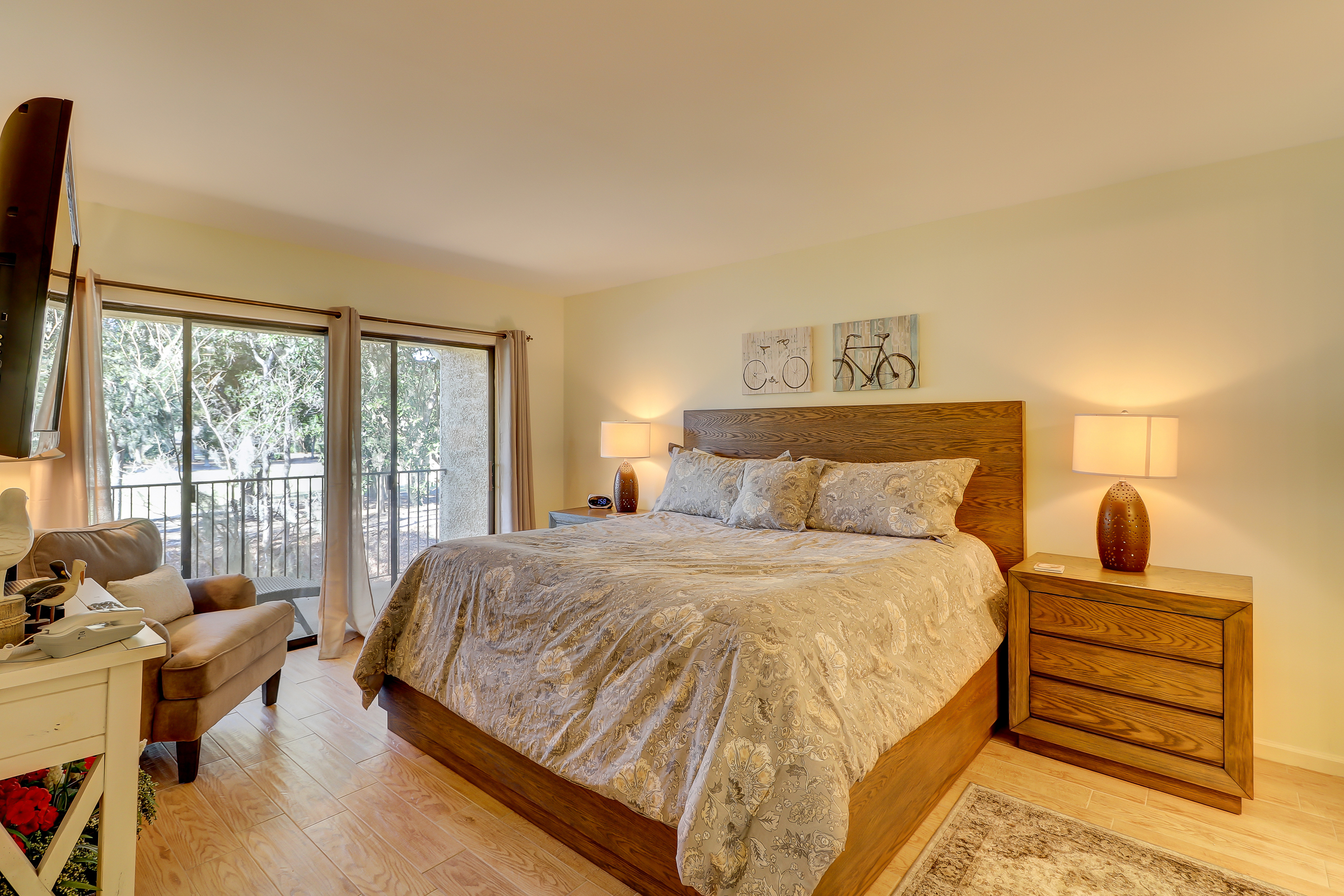 The master bedroom has a king bed, wall-mounted flat panel TV, access to the covered balcony and an en suite bath with tub/shower combo