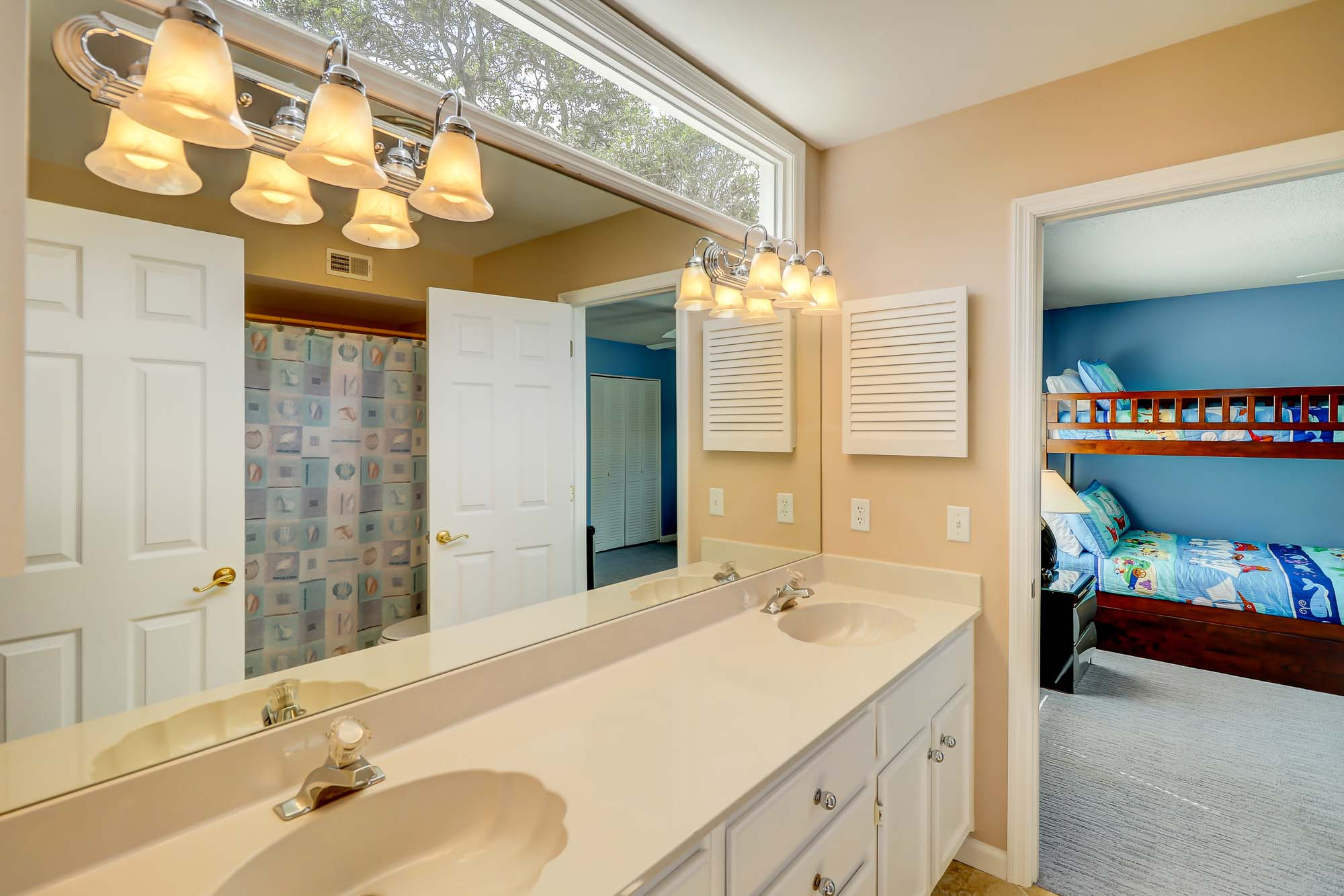 Jack and Jill bath shared between bedrooms 3 and 4 on lower level has dual vanities and tub/shower combo