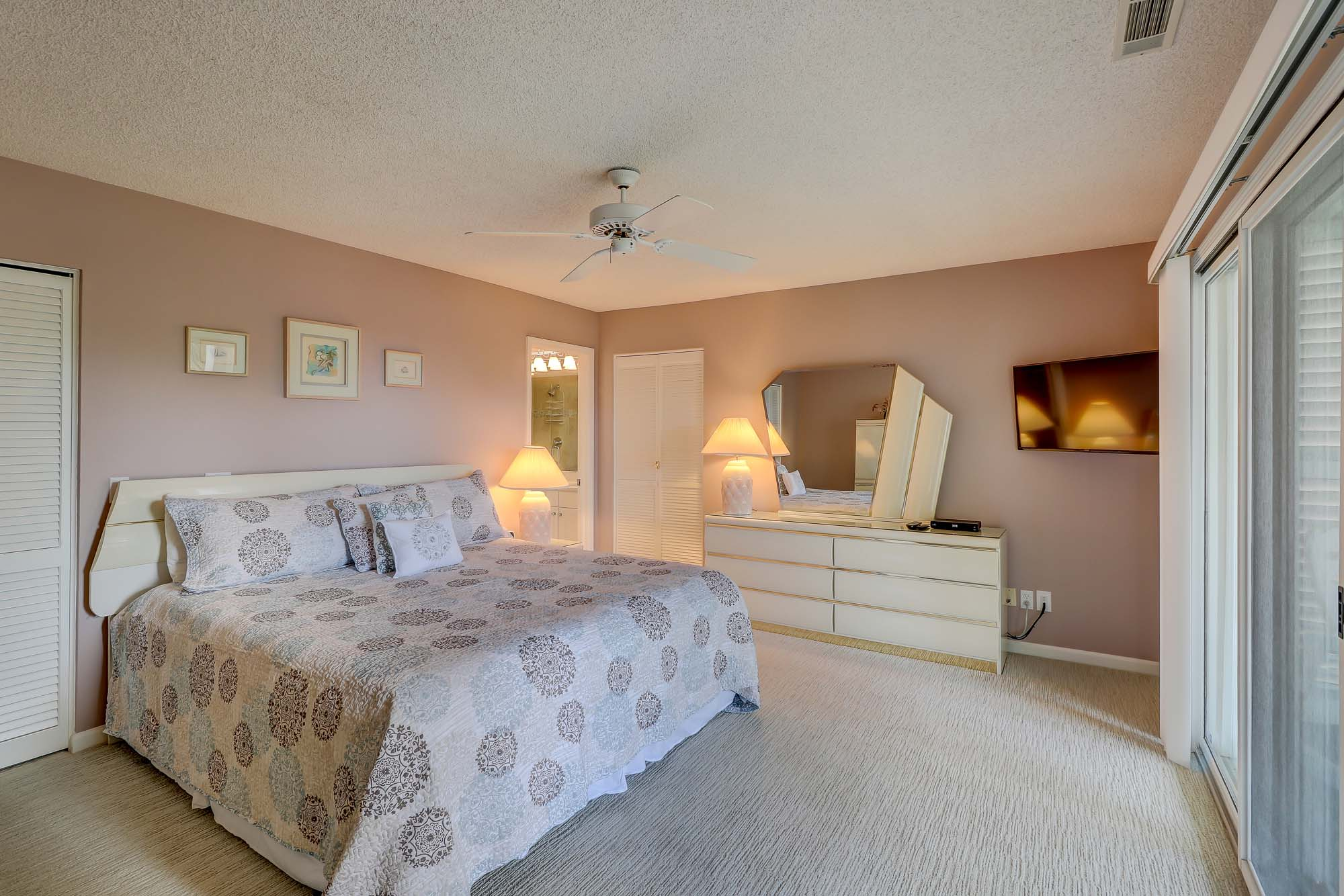 King suite (downstairs master, bedroom 1 in description) has king bed, wall-mounted flat panel TV, private en suite bath with soaking tub and walk-in shower with accupressure stone floor, and access to covered front porch