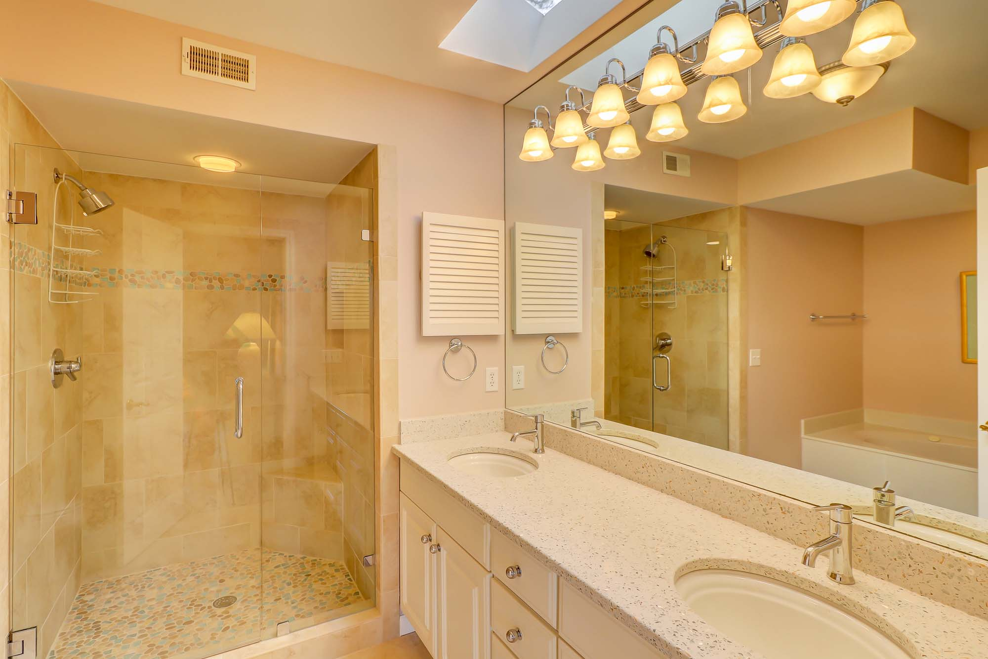 Downstairs master bath has dual vanities, soaking tub and glass-enclosed walk-in shower with accupressure stone floor (if you've never tried one, you need to!)