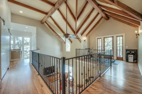 This open air second floor is a wrap-around and is accented by the lovely beamed vaulted cathedral ceiling in the home.