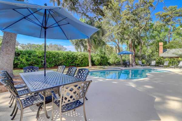 The pool deck has dining tables with umbrellas, chaise loungers and additional seating for backyard relaxation and al fresco dining
