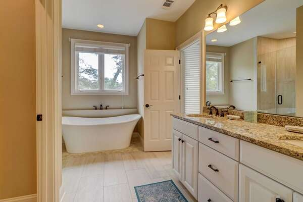 Upstairs master bath has soaking tub, glass-enclosed walk in shower and dual sink vanity